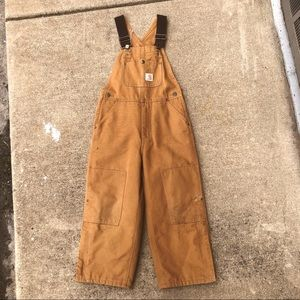 It's worn in classic canvas Carhartt overalls